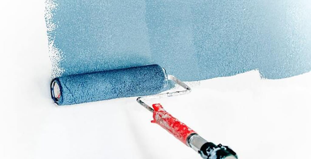 blue paint roller, rolling on blue paint to a white wall
