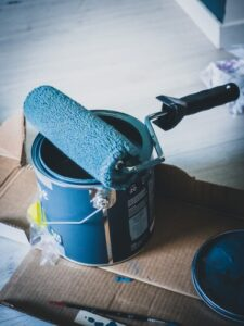 Blue paint with a blue rolling brush on top of paint can